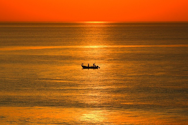 Lonely fisherman's boat in a golden sea