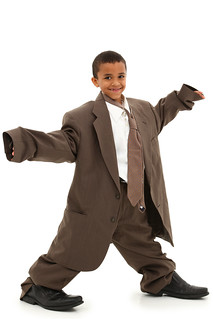 Adorable Handsome Black Boy Child in Baggy Business Suit laughing and walking over white background. | by aqua.mech