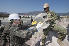 U.S. Navy Construction Mechanic 3rd Class Brian Rosette, assigned to Naval Mobile Construction Battalion (NMCB) 4, passes a concrete block to a Republic of Korea Seabee during pier repair training for exercise Foal Eagle in March. (U.S. Navy/MCC Lowell Whitman)