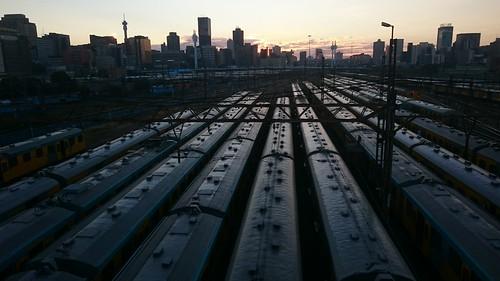 city skyline sunrise dawn trains johannesburg carriages parkstation braamfontein hillbrowtower doubledeckerhighway m1south