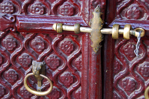 A red door with brass fittings in the Udaipur Palace in India