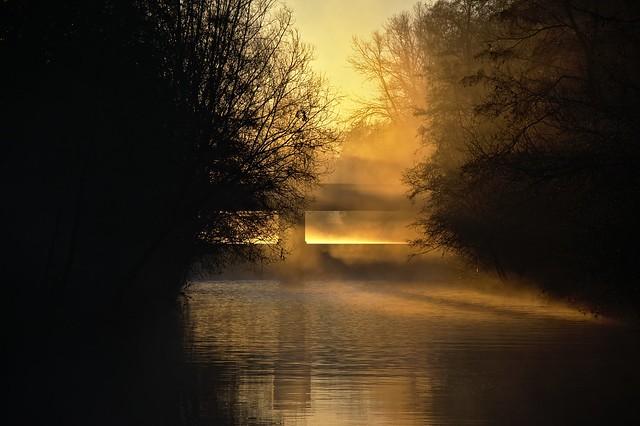 Weir in sunrise mist
