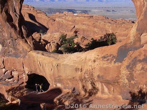 Two children in the bottom of Double O Arch in the Devils Garden Area of Arches National Park, Utah