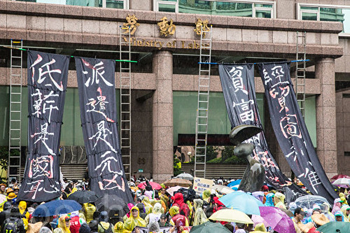 圖04.遊行群眾在勞動部掛起反低薪的黑色凡幡布條