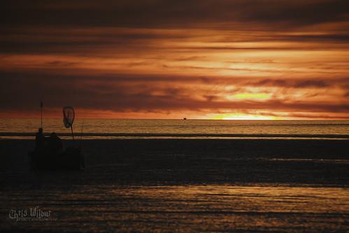 dawn sunrise dramatic sky sun silhouette moody horizon lake ontario red fish fishing people boat water