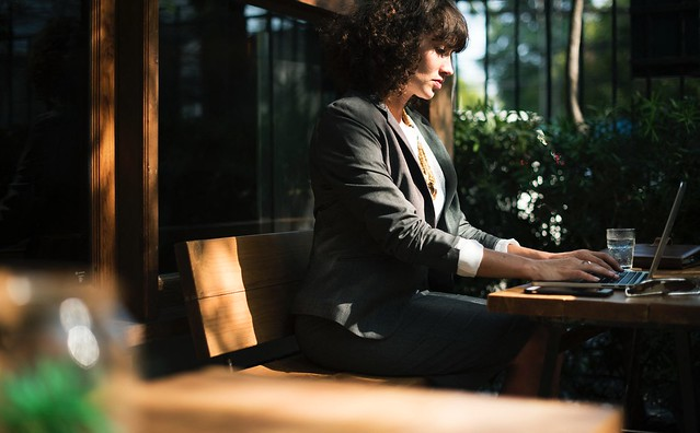 Businesswoman Sitting Outside with Laptop - Credit to https://bestpicko.com/