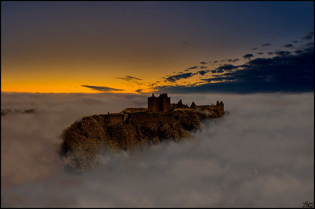 mountaintop seen from above a sea of clouds, old castle ruin seen on top