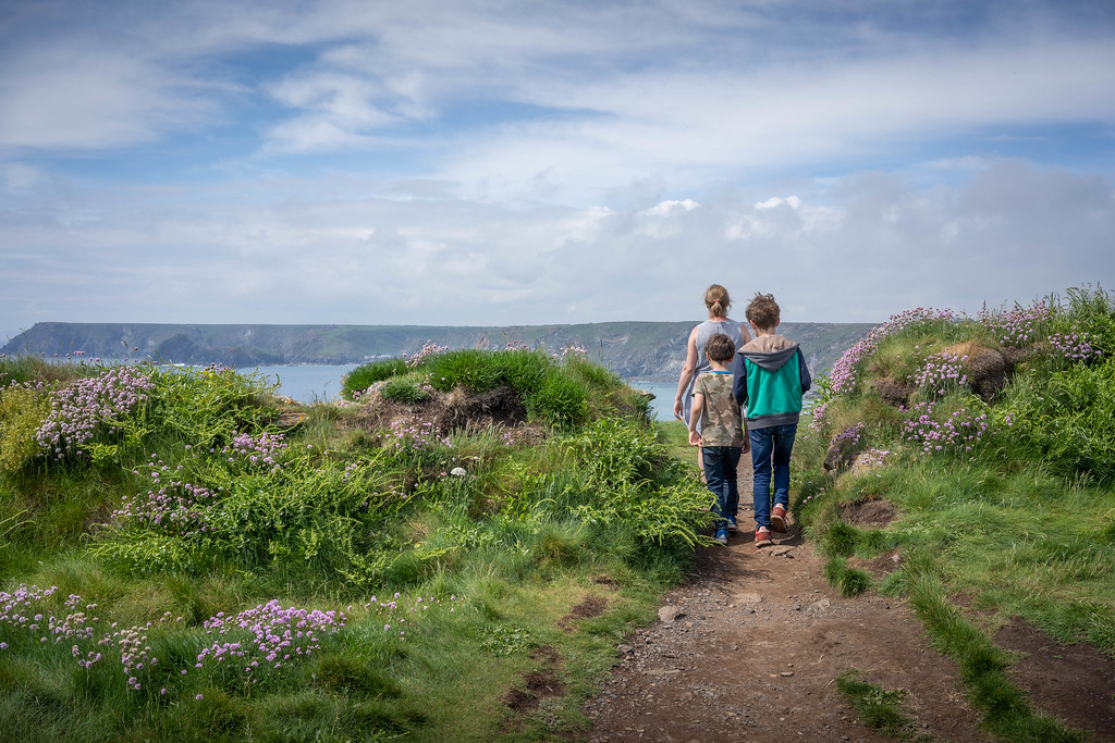 Family walking along the cliff top at The Lizard, Cornwall