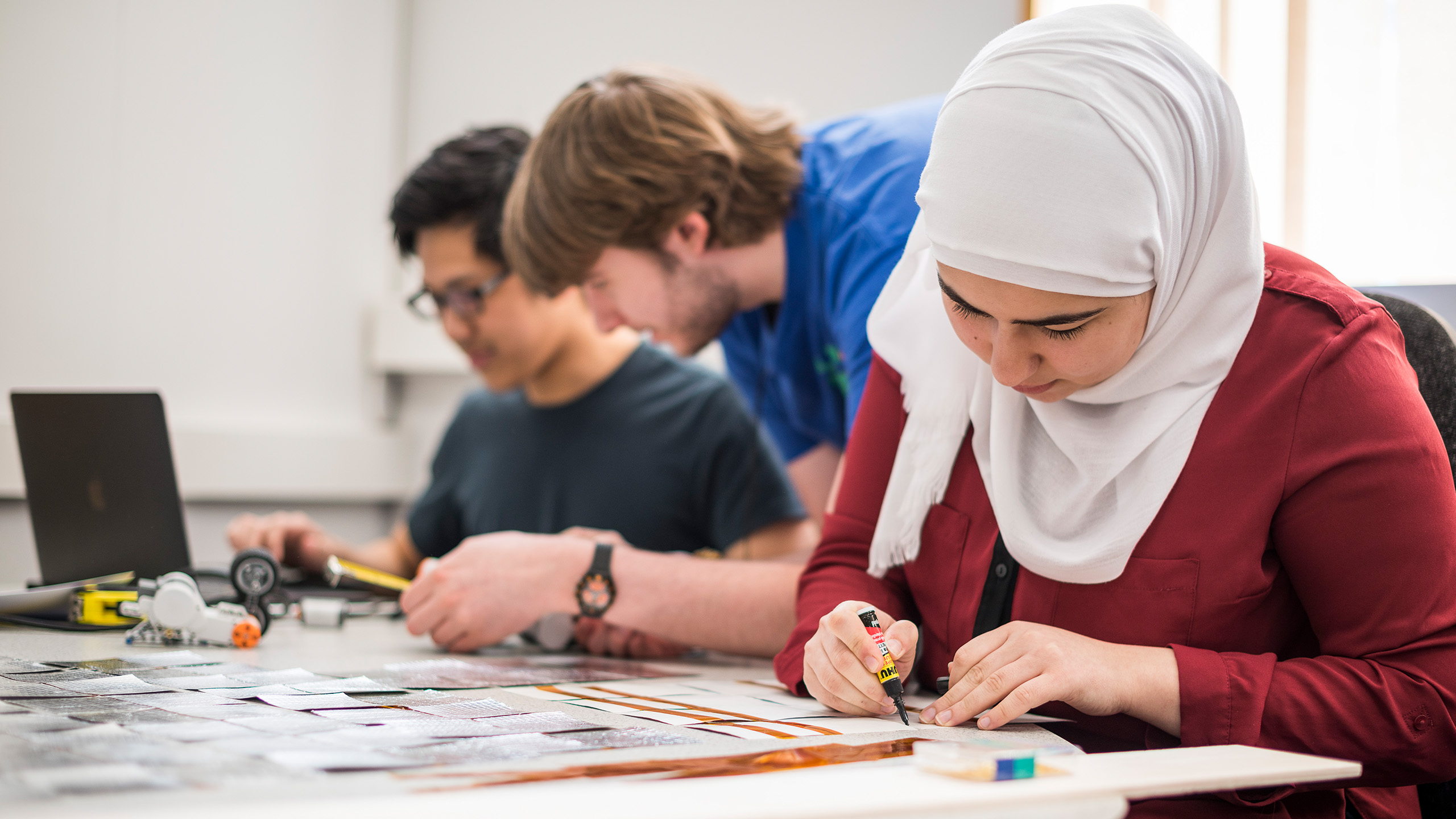 Students, two male and one female, working on a project
