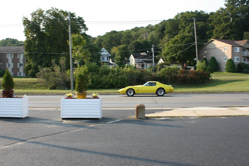 petoskey michigan north northern town village city picturesque summer september 2012 swirls ice cream stand parlor drivein americana american flag fence dusk late afternoon happy good times 1000 bay view rd beaubien ave bayfront park feels roadside red white blue outdoor 1977 chevrolet chevy corvette stingray yellow moving motion inmotion worldcars