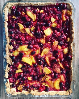"""Today in project """"use up my baking stash before we move house"""": I made a tart with some of the cranberries I froze at Christmas, along with a couple of peaches. Olive oil pastry from @food52, frangipane adapted from @lazycatkitchen. #bakestagram #cranberr"""