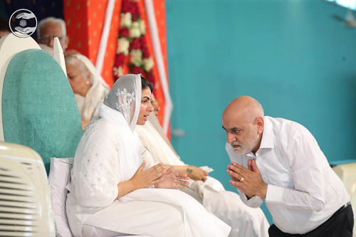 Puts the white scarf (Dupatta), around Rev. Sudiksha Ji's neck through a devotee.