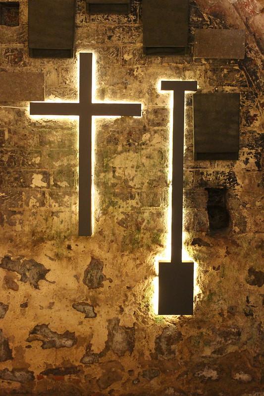 Ein Kreuz und ein Spaten hängen vor einer Wand und werden von hinten beleuchtet.