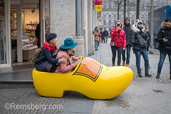 Young women play in a giant yellow shoes in streets of Amsterdam, Netherlands
