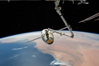 The SpaceX Dragon cargo craft is pictured in the grips of the Canadarm2 | by NASA Johnson