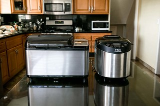 Bread machines from Zojirushi and T-fal on kitchen countertop with matching stainless steel appliances | by yourbestdigs