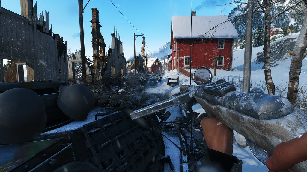 Screen capture from the game Battlefield V showing a gun being pointed down a snow-covered street near the mountains