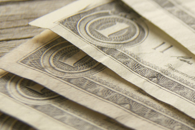 Close up of fanned dollar bills on wood