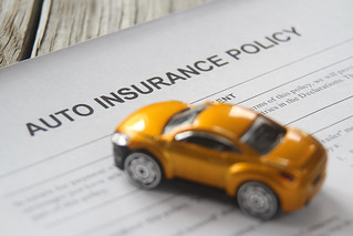 Auto insurance policy with small toy car | by QuoteInspector.com