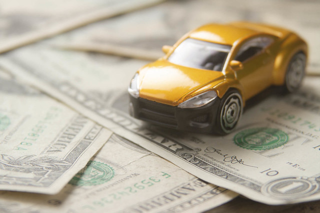 Car Insurance - Toy Car on Pile of Dollar Bills
