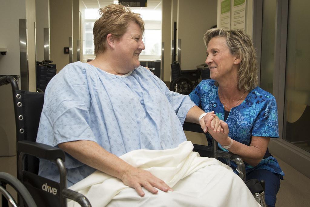 patiente en chaise roulante qui tient la main d'une autre femme
