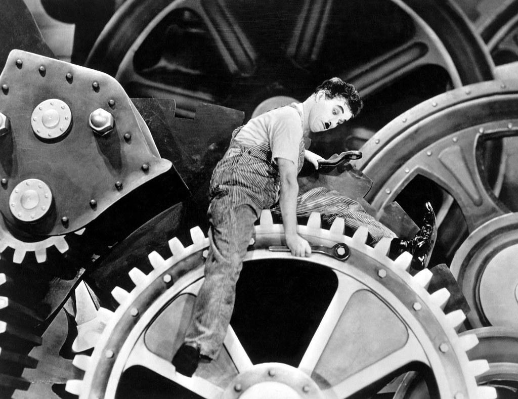 """Cena do filme """"Tempos modernos"""", de Charles Chaplin. Operário em engrenagem gigante"""