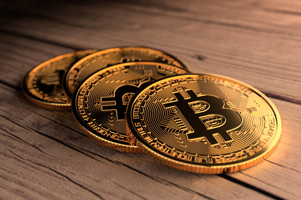 Four Bitcoins laid on wood planks