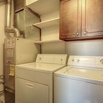 Washer and dryer in the utility area, with storage both behind cabinet doors as well as exposed shelves.