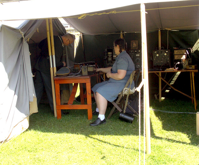 LADY GERMAN RE-ENACTOR WEARING A BLUE DRESS AND ANKLE SOCKS BLACK SHOES AND PLAT'S IN HER HAIR SITTING IN A RADIO SHACK TENT WITH A MALE GERMAN OFFICER STANDING AT THE ROYAL GUNPOWDER MILLS VE DAY EVENT 2018 CELEBRATION IN AN EAST LONDON BOROUGH SUBURB ST