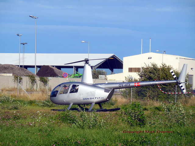 DanishFly.dk OY-HTF 2006 Robinson R44 C/n 11454 prepares to take off from vacant lot