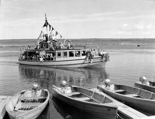 The motorboat Queen returns to Waskesiu pier from an all-day cruise to Kingsmere Portage... / Le bateau à moteur Queen retourne à la jetée de Waskesiu après une croisière d'un jour au portage Kingsmere...