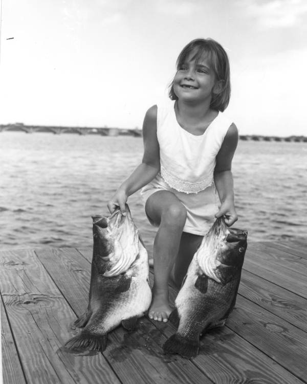 Teri Lynn Hargis happily holding two large bass at a dock - Palatka