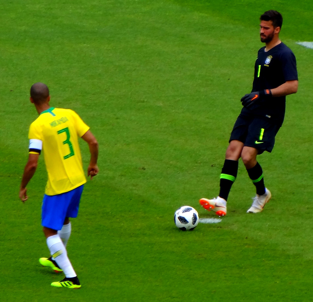 Brazil goalkeeper Alisson plays a pass to defender Miranda
