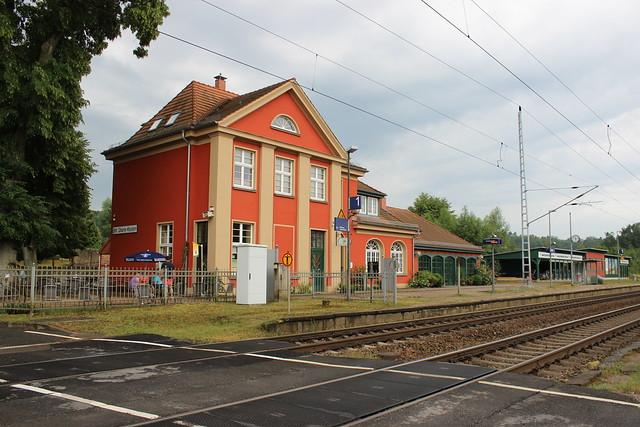 Ein orangenes Bahnhofsgebäude, im Vordergrund zwei Gleise