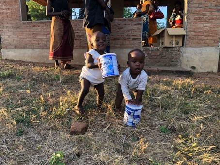 Aquí una pareja de gemelos recibiendo leche infantil recibida en el contenedor