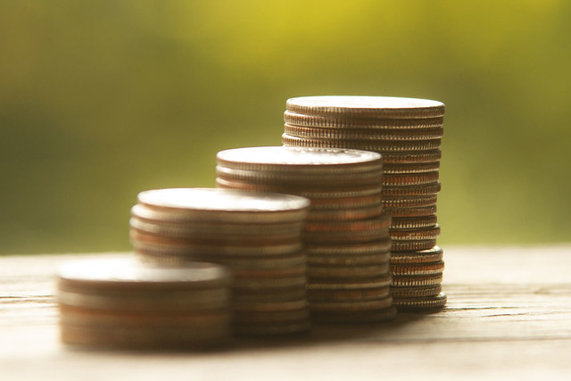 Increasing stacks of coins with bokeh