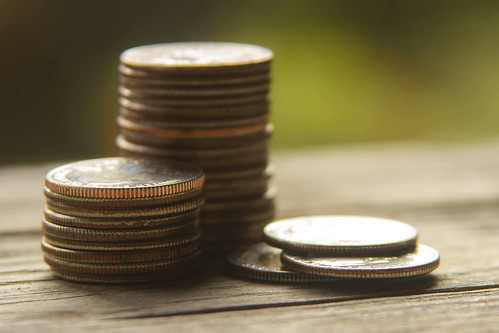 Stacked quarters on wood with bokeh | by QuoteInspector.com
