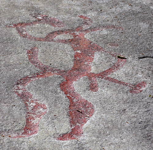 Bronze Age petroglyphs of a man possibly playing a musical instrument chipped out of the granite at Tanum World Heritage Rock Art Centre in Sweden