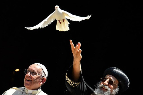Pope Francis (L) watches as Egypt's Coptic Orthodox Pope Tawadros II releases a dove after a meeting with other religious leaders at the Pontifical Basilica of St Nicholas in Bari, in the Apulia region in southern Italy, on July 7, 2018. (Getty) | by Al-Majalla