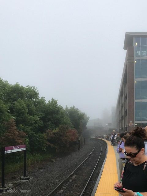 Commuters await a late train on a foggy morning.
