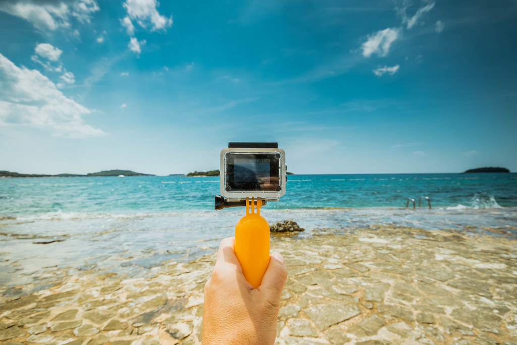 Man holding underwater camera (like GoPro) at the beach