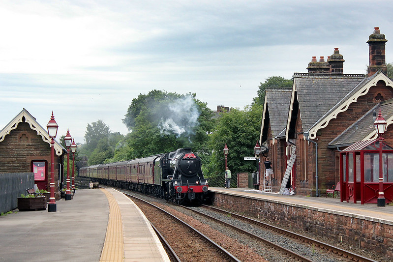 The painters are busy putting another coat on th woodwork of the station building at Lazonby, as 8F No.48151 rattles through with the northbound Dalesman working.