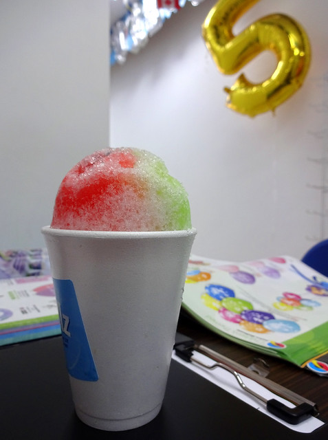 A white paper cup with a heap of shaved ice poking out the top, coloured with red and green syrups.  In the background a large gold balloon in the shape of the number 5 hangs against a white-painted wall.  A couple of catalogues are open on the table next to the cup.