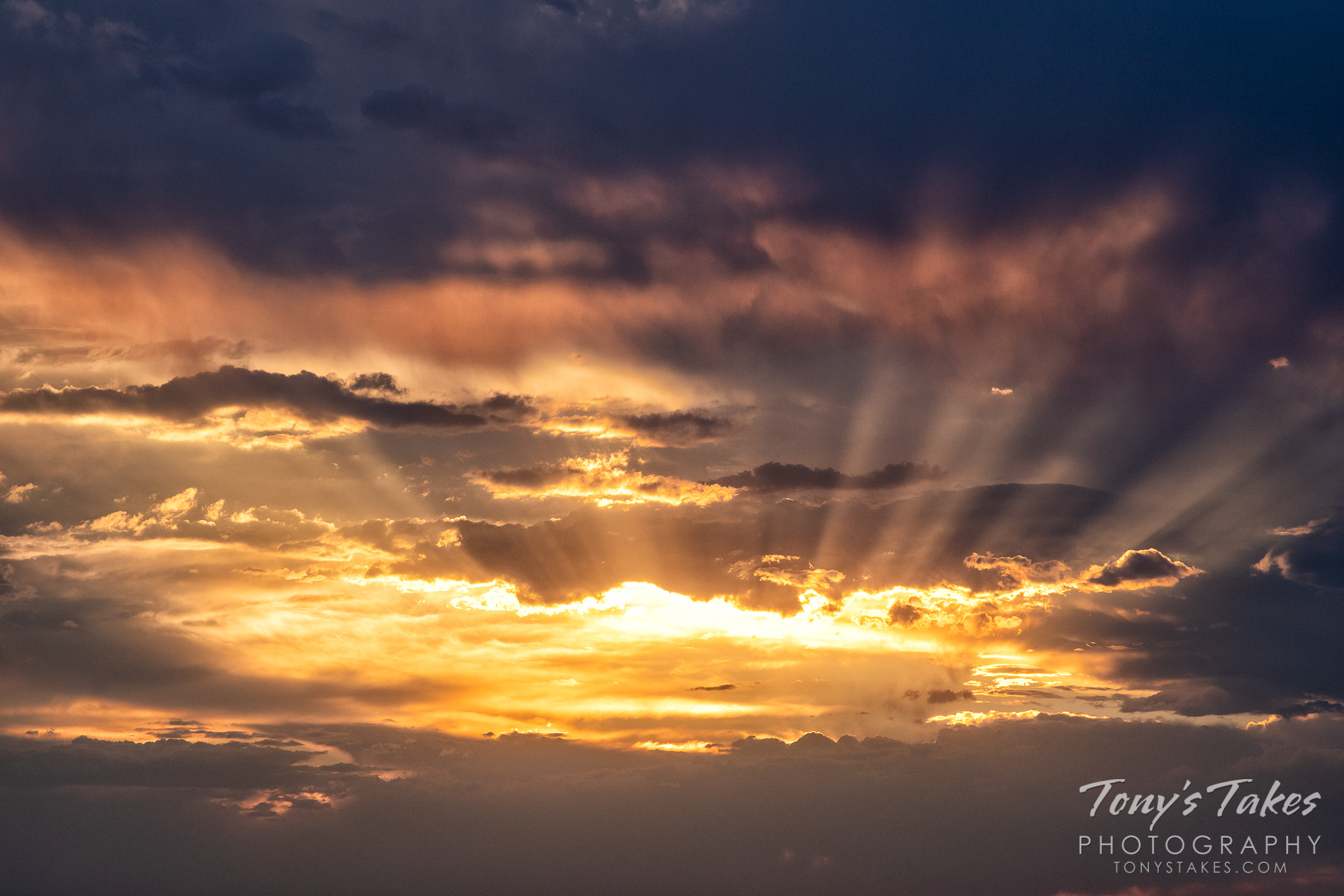 Crepuscular rays emanate from sunset at North Sterling State Park in Colorado. (© Tony's Takes)