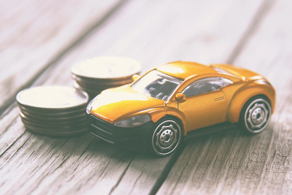 Car Insurance - Small car next to coin stacks
