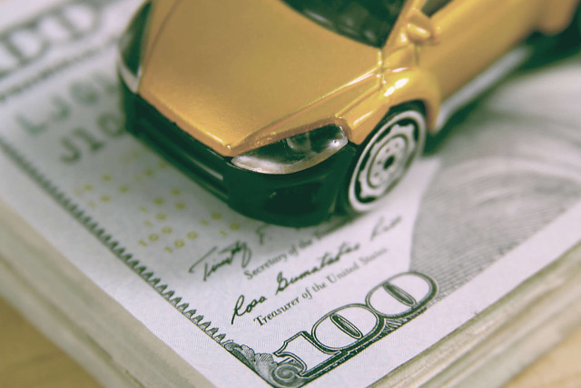 Toy car on stack of cash