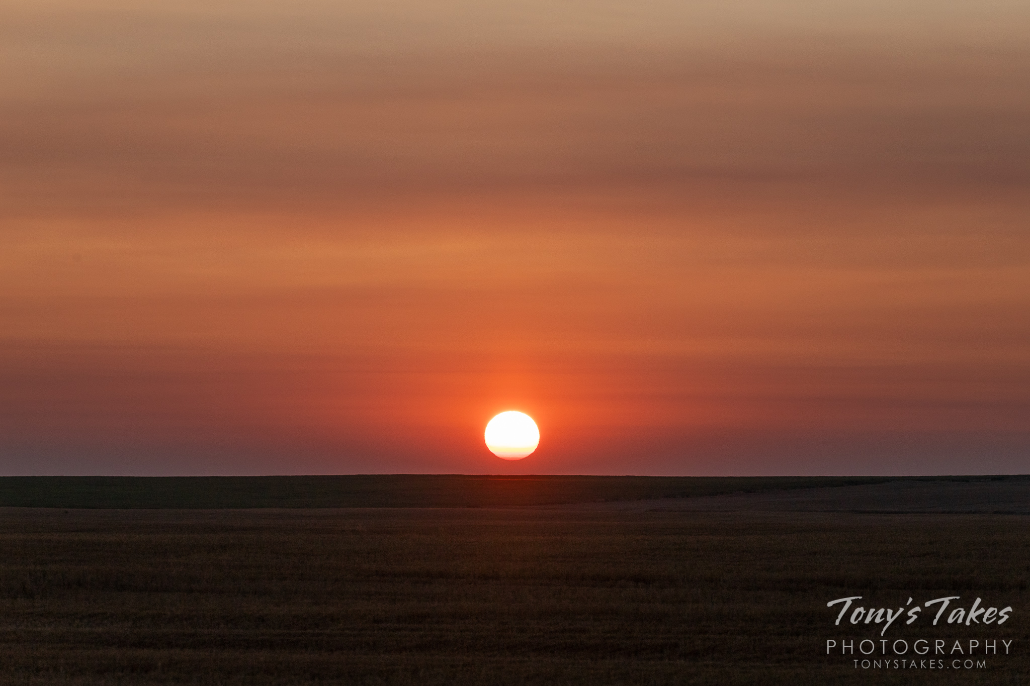 Smoke from wildfires in California and Canada colors the sunrise on Colorado's plains. (© Tony's Takes)