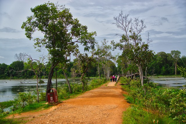 Path to Neak Pean temple ruins through the Jayataka baray in Angkor Archeological Park near Siem Reap, Cambodia