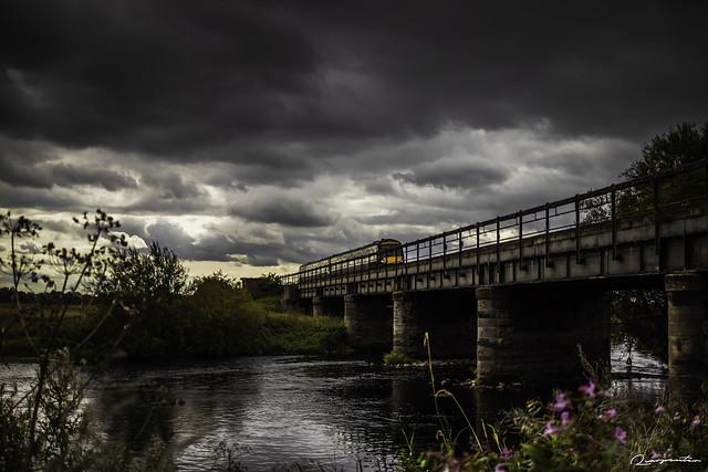 Train crossing bridge over river
