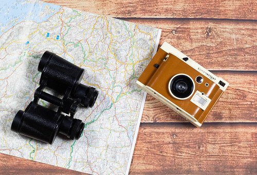 Old vintage camera and binoculars on a old world map | by wuestenigel
